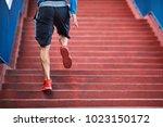 back view of a man running up a ...   Shutterstock . vector #1023150172
