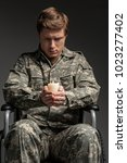 Small photo of Portrait of cheerless handicapped male veteran holding candle and looking at it. He is sitting in invalid chair with sad look. Isolated on grey background