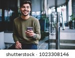 Small photo of Happy bearded hipster guy excited with good news receiving message on smartphone sitting on urban settings, cheerful handsome man satisfies with mobile tariffs for calls and messages chatting on phone