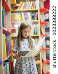 pretty school girl in library...   Shutterstock . vector #1023388222