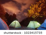 glowing tent in the mountains... | Shutterstock . vector #1023415735