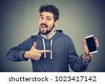young cheerful man showing new... | Shutterstock . vector #1023417142