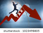 businessman jumping over tax in ... | Shutterstock . vector #1023498805