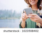 smiling woman using mobile... | Shutterstock . vector #1023508402