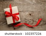 gift box with red bow on wood... | Shutterstock . vector #102357226