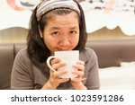 young woman drink coffee and... | Shutterstock . vector #1023591286