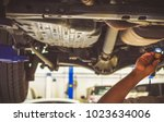 Small photo of Mechanic inspects car suspension system and chassis with a torch-lite under the car.