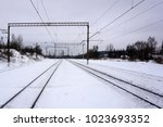 Small photo of The rails of the railway go far along the snow-covered ground.