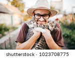 Stock photo happpy young bearded farmer holding two little kitten in hands outdoor in village with abstract 1023708775