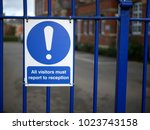 Small photo of Concept of school security or stranger danger shown by visitors must report to reception sign on blue fence in front of British girls secondary grammar school