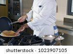 cook at work in a restaurant... | Shutterstock . vector #1023907105