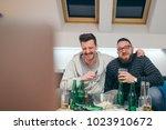 friends watching sport on tv at ... | Shutterstock . vector #1023910672