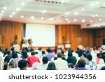 blurred photo of speaker at... | Shutterstock . vector #1023944356