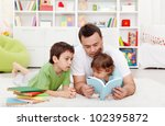 Father reading stories to his boy children at home - stock photo