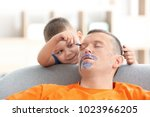Stock photo little boy painting his father s face while he sleeping april fool s day prank 1023966205