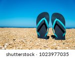 blue flip flops on the sand   a ... | Shutterstock . vector #1023977035