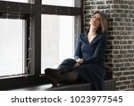 young beautiful girl sits on a... | Shutterstock . vector #1023977545