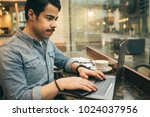 young arabic guy using computer ... | Shutterstock . vector #1024037956