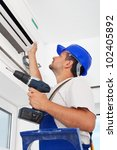 Small photo of Worker installing air conditioning unit - closeup