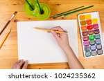 kids hand holding a pencil on... | Shutterstock . vector #1024235362