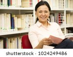 Small photo of Happy mature Asian woman smiling to the camera enjoying reading a book at the library copyspace coziness education recreation happiness maturity literature learning teacher profession occupation