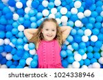 child playing in ball pit.... | Shutterstock . vector #1024338946