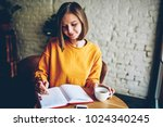 dreamy young woman writing down ... | Shutterstock . vector #1024340245