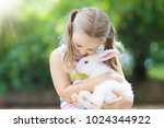 child playing with white rabbit.... | Shutterstock . vector #1024344922