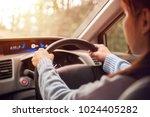 woman driving car at sunlight. | Shutterstock . vector #1024405282