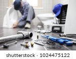 Small photo of plumber at work in a bathroom, plumbing repair service, assemble and install concept