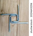 Small photo of Allen key arranged in square shape on wood background
