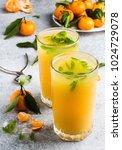 tangerine juice in glasses on... | Shutterstock . vector #1024729078