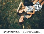 young couple lying on the grass ... | Shutterstock . vector #1024923388