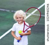 Small photo of Child playing tennis on outdoor court. Little boy with tennis racket and ball in sport club. Active exercise for kids. Summer activities for children. Training for young kid. Child learning to play.