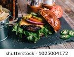 cheeseburger on a pretzel bun... | Shutterstock . vector #1025004172
