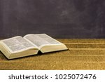 bible on a gold table.... | Shutterstock . vector #1025072476