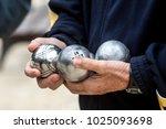 An Older Man Holds 3 Petanque...