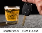 Small photo of finger hold a car key in front of cup of beer concept of drunken driving