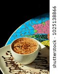 Small photo of Coffee mocha decorate with chocolate on white cup on colorful mosaic table.