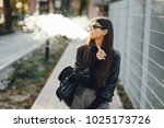 stylish girl smoking an e...   Shutterstock . vector #1025173726