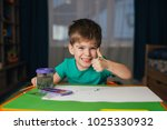 Small photo of Little boy draws a brush and paint his first picture. Focus at the drawing