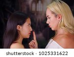 Small photo of Young mad american blonde woman, putting her finger in the mouth of a foreign woman, pretending to keep her in silence of violence and racism. Racism, violence or discrimination concept in a blurred