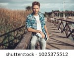young man standing on a bridge... | Shutterstock . vector #1025375512