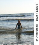 little girl playing in the waves | Shutterstock . vector #1025413096