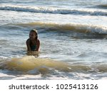 little girl playing in the waves | Shutterstock . vector #1025413126