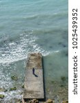 Small photo of Six-year-old boy in jacket and jeans is standing on pier at sea during a storm with waves afar view