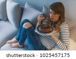depressed woman eats cake.  sad ... | Shutterstock . vector #1025457175