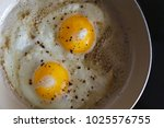 fried eggs from 2 eggs in a... | Shutterstock . vector #1025576755