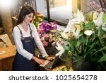 women florist looking laptop... | Shutterstock . vector #1025654278