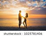 couple on beach at sunset... | Shutterstock . vector #1025781406